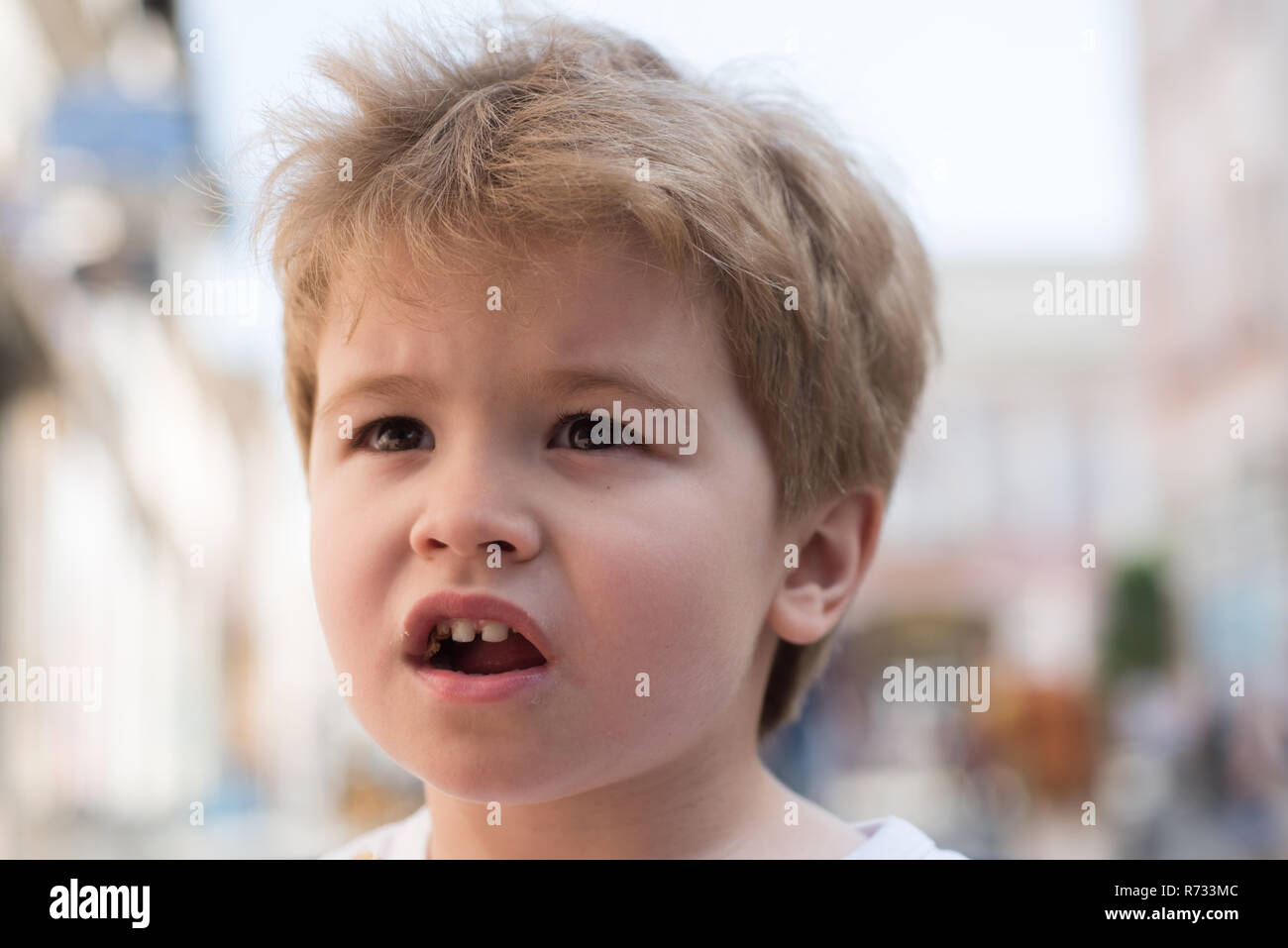 Trendiest haircut. Little child eating outdoor. Small boy with stylish haircut. Little child with short blond hair. Healthy hair care habits. Its always important to me to take good care of my hair Stock Photo