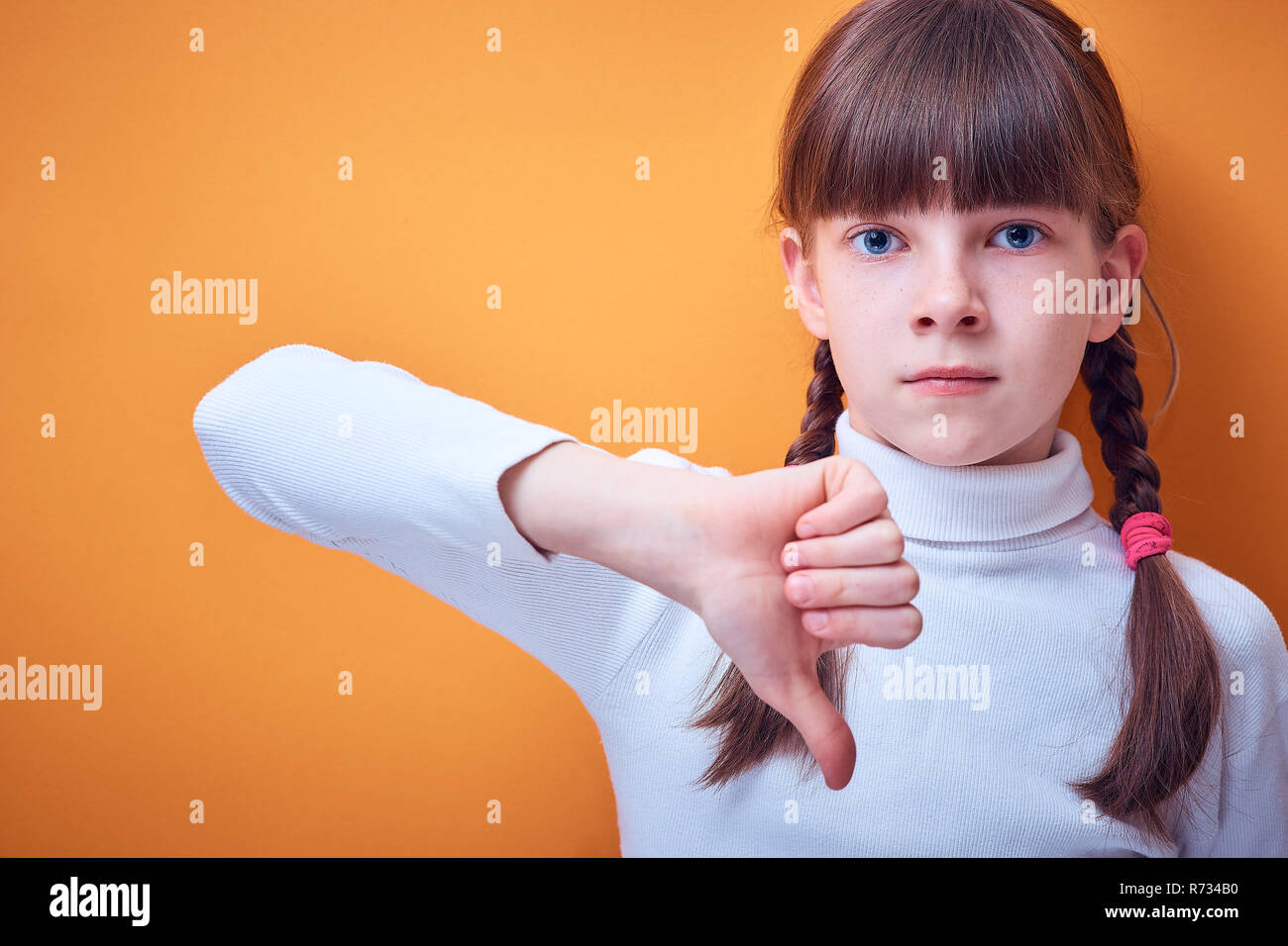 disagreement and protest, Caucasian teen girl shows thumb down on colored background, place for text - Stock Image