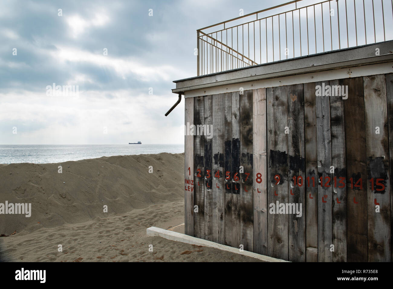 Facades covered with wooden planks to protect against winter weather and storms of the sea, in front of the building a sand dune, on the bottom an oil - Stock Image