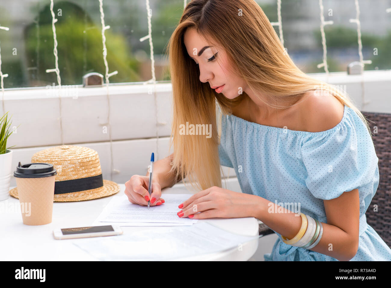 Beautiful girl in blue dress, tanned skin with long hair. Summer sitting in a cafe. He holds a pen in his hands and fills important documents, signs a contract, draws up a legal document in writing. - Stock Image