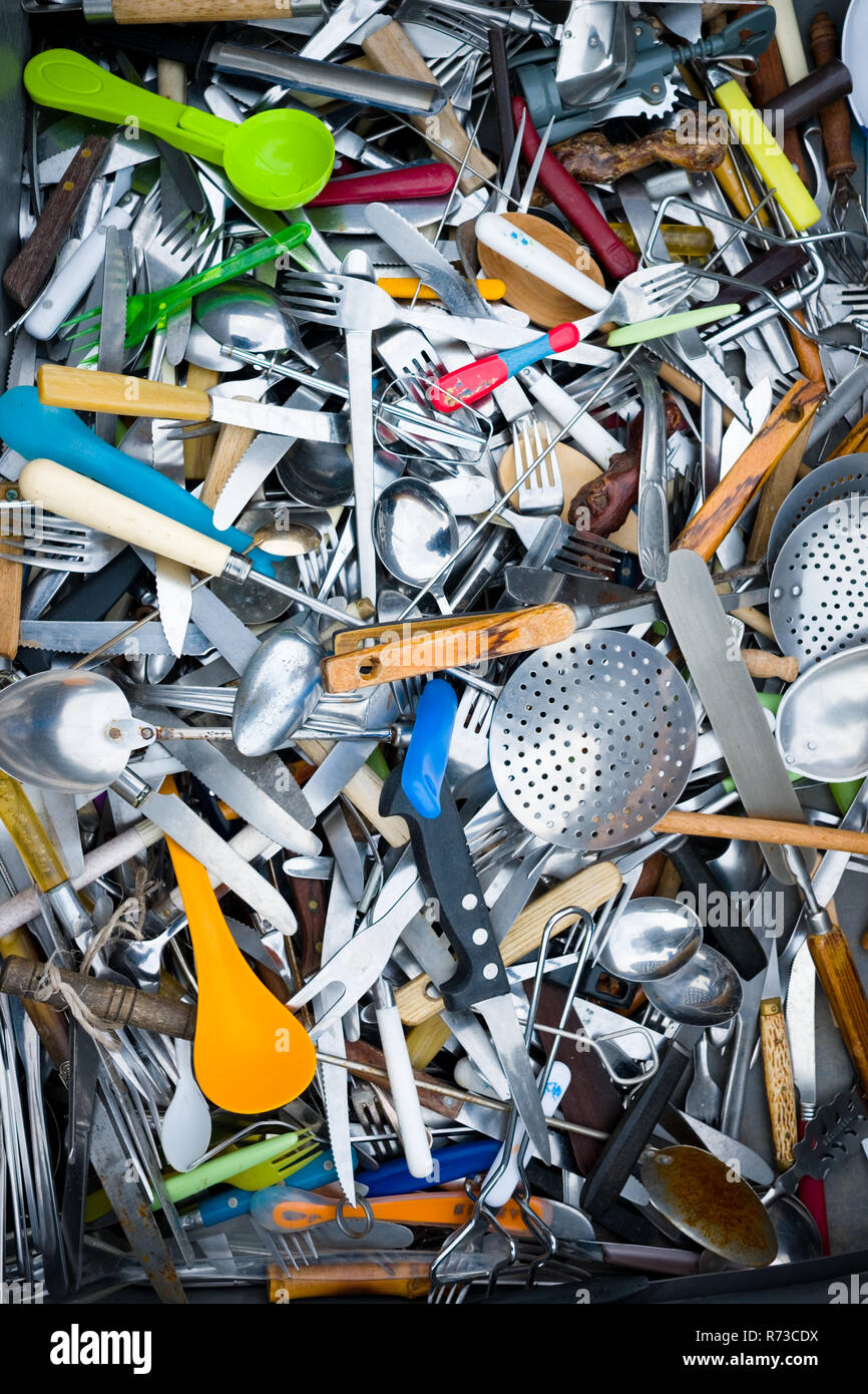looking down into an assorted pile of mixed secondhand cutlery and cooking utensils in a huge box - Stock Image