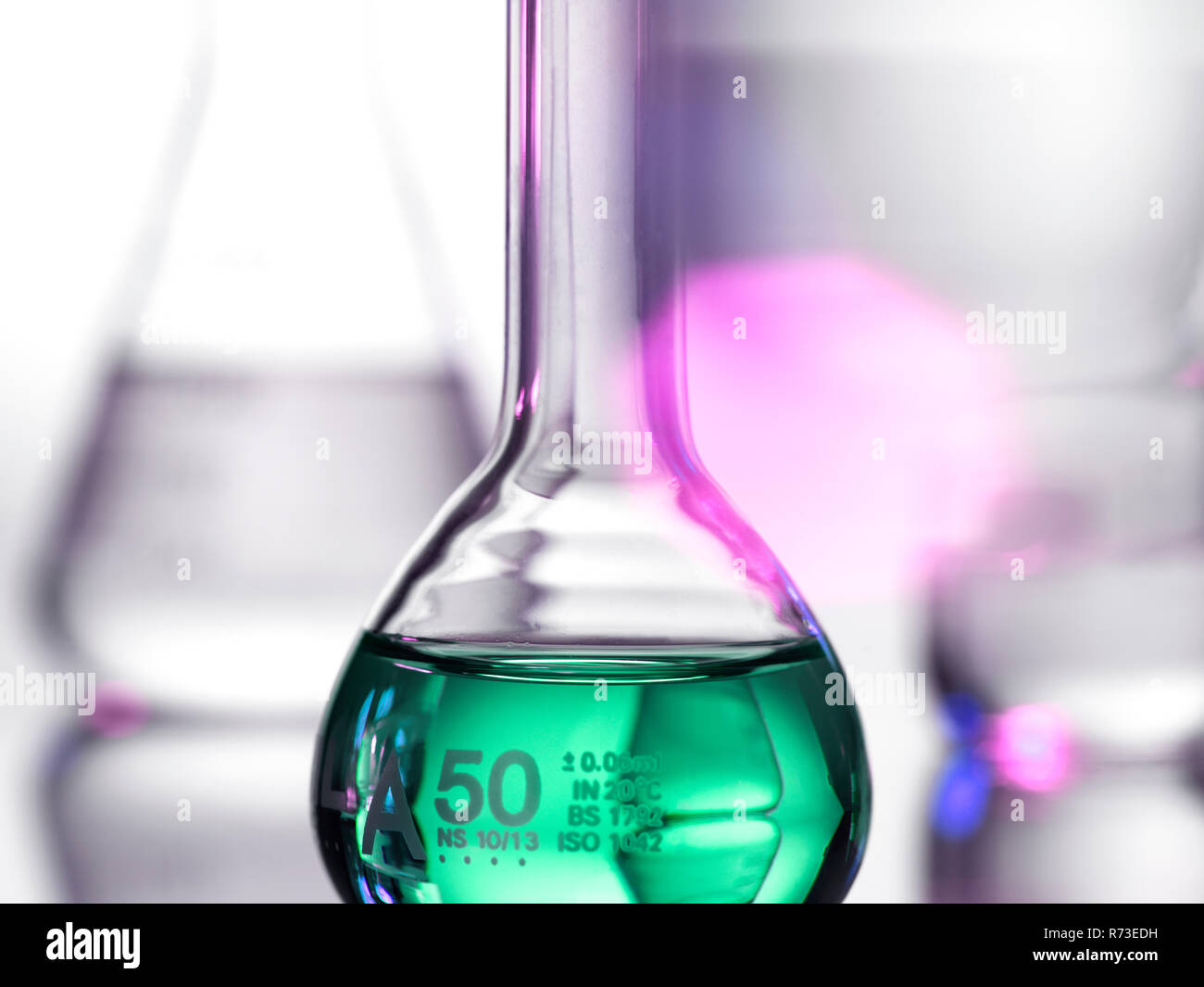 Laboratory beakers containing chemical formulas - Stock Image