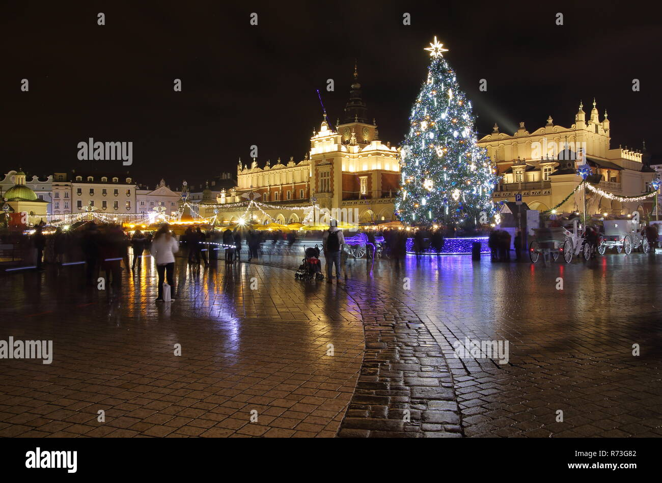Krakow city scape with big Christmas tree, historical illuminated buildings, at night, beautiful reflections on wet ground, people, long exposure. - Stock Image