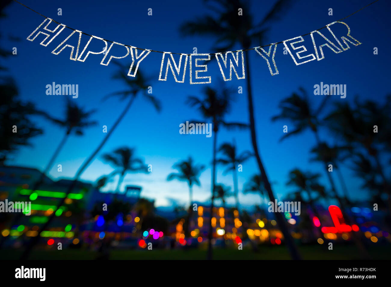 happy new year message hanging in glittery party bunting above tropical palm trees of the glowing