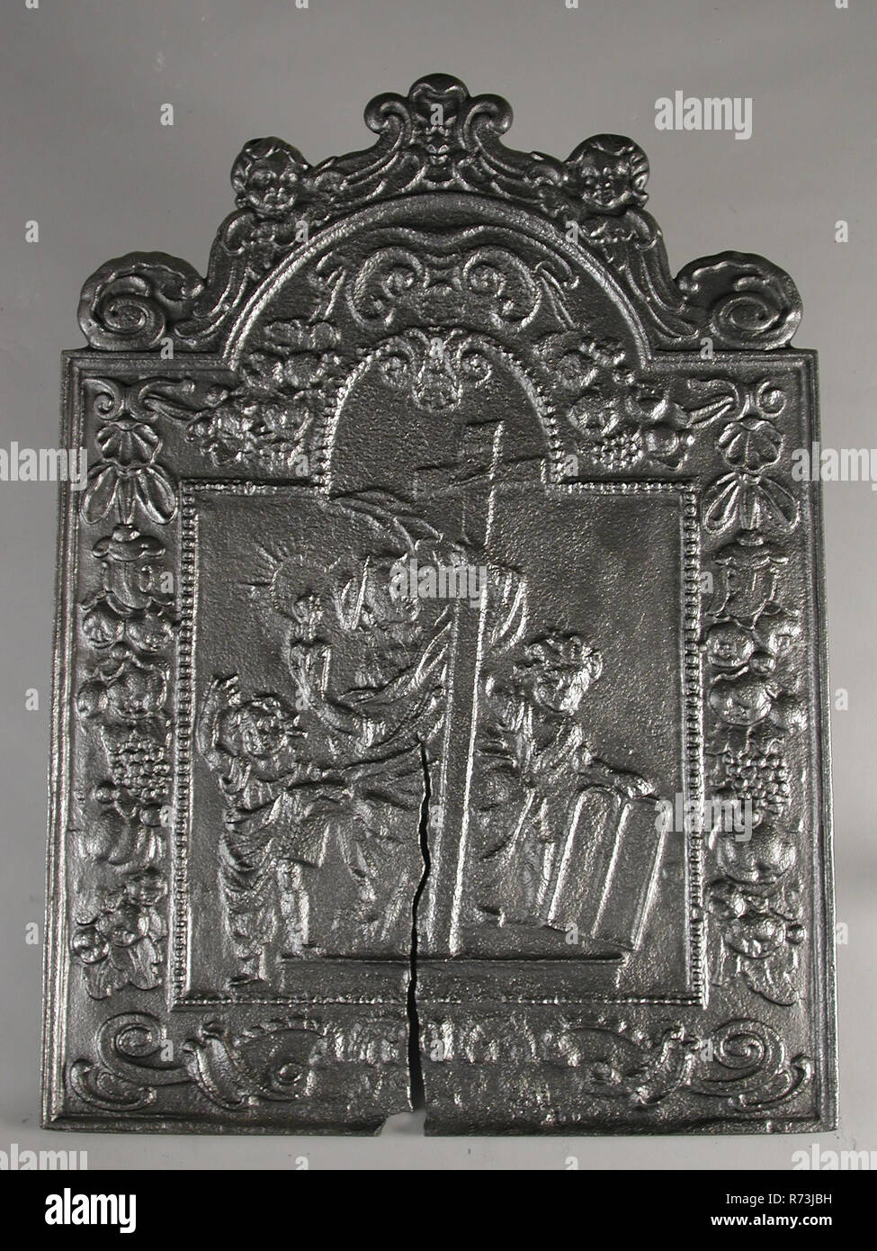 Fireback woman with cross and lamp, the Faith, hob plate cast iron, cast Rectangular with arch at the top. On top of two putti with volutes Wide edge between frame and pearl necklace decorated with fruit-eaters In the middle picture of female figure holding large cross. She holds burning lamp in the right hand. She is accompanied by two children: the judge holds the tablets of the law living environment interior heating Faith religion Christianity Ten Commandments - Stock Image