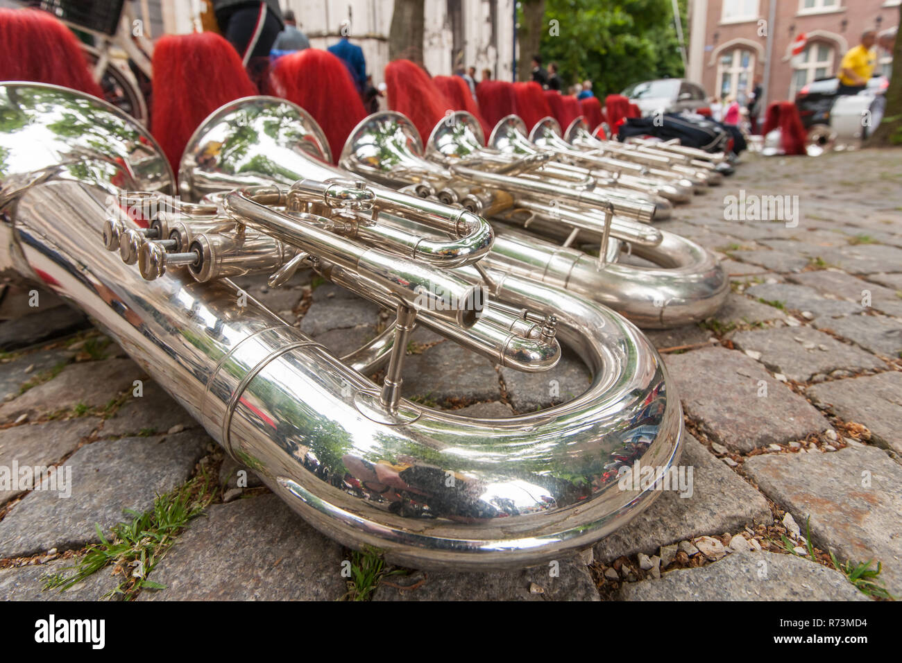 Details from a music, show and marching band. Composition of helmets and wind instruments, baritone on the street. - Stock Image