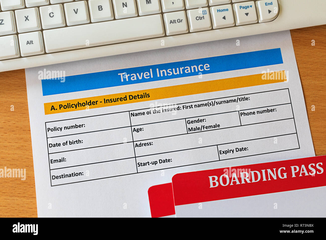 Travel insurance form on wooden table with boarding pass ticket and keyboard. Agencies sell airplane tickets or travel packages and allow consumers to - Stock Image