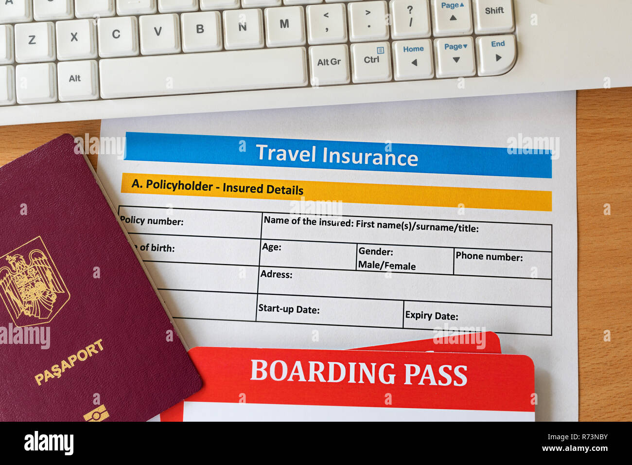 Travel insurance form with boarding pass tickets, passport keyboard on wooden table. Agencies sell airplane tickets or travel packages and allow consu - Stock Image