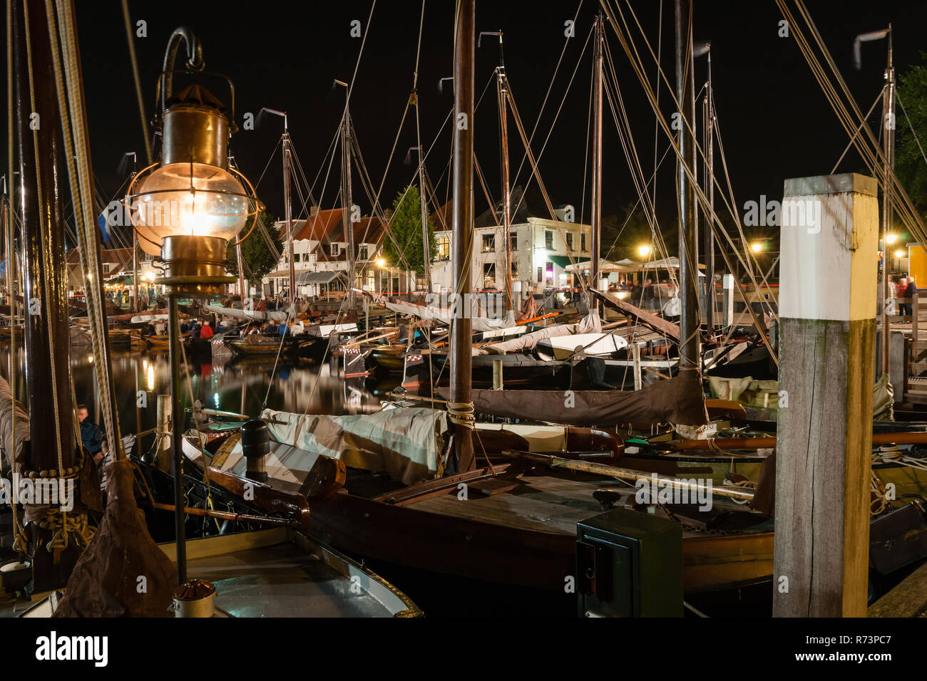 Harbor with wooden flat bottom ships and fishing boats tied up at the quay. - Stock Image