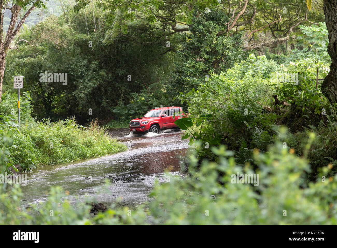 A truck crosses a stream during a rainstorm in the Waipi'o Valley on the Big Island of Hawaii. - Stock Image