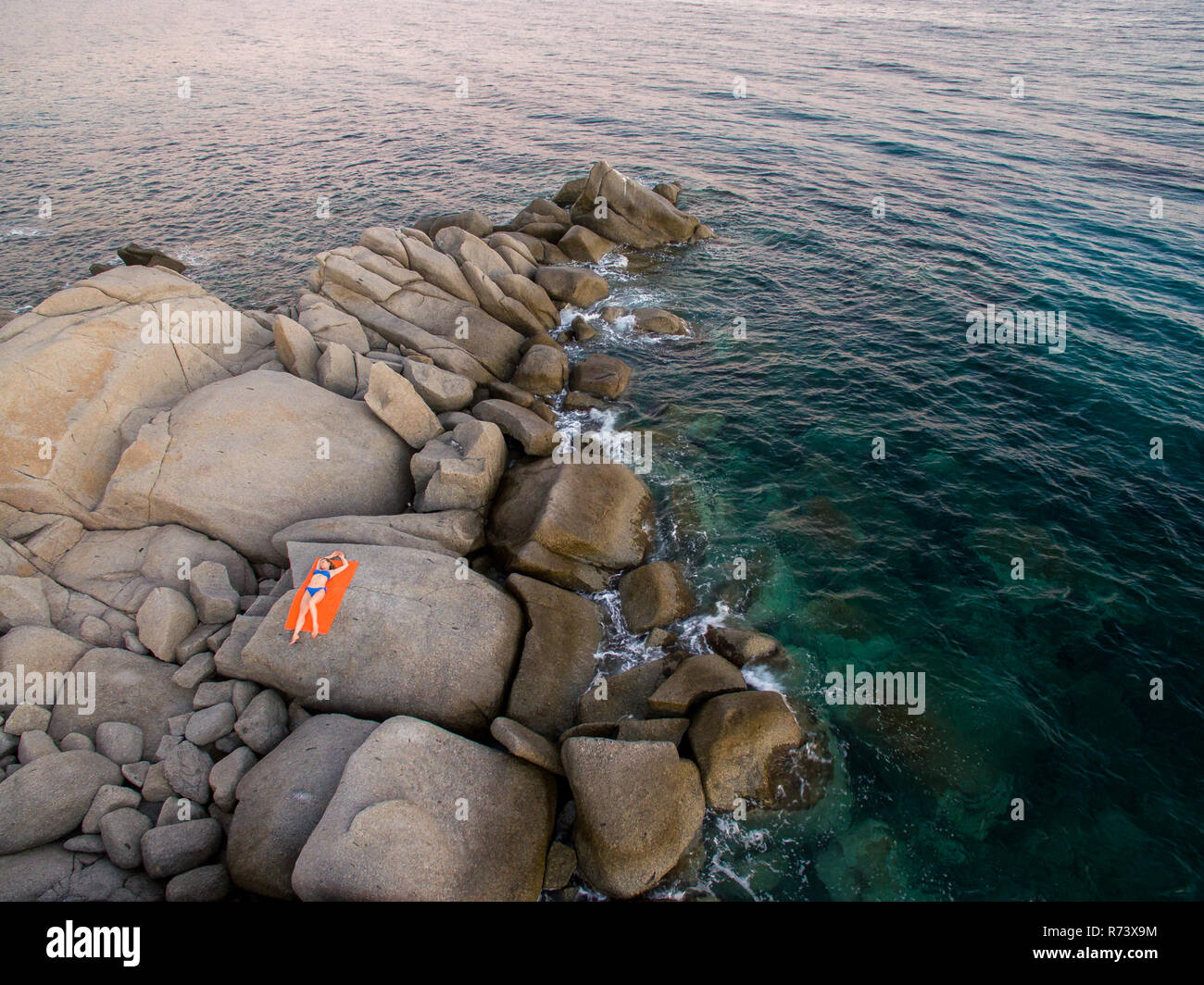 Aerial photography of the Sardinia coast during a summer sunset. Small waves on the rocks taken with a drone. - Stock Image