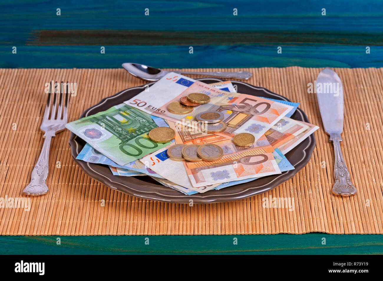A plate full of money ready to be eaten with cutlery on top of an Asian tablecloth. - Stock Image