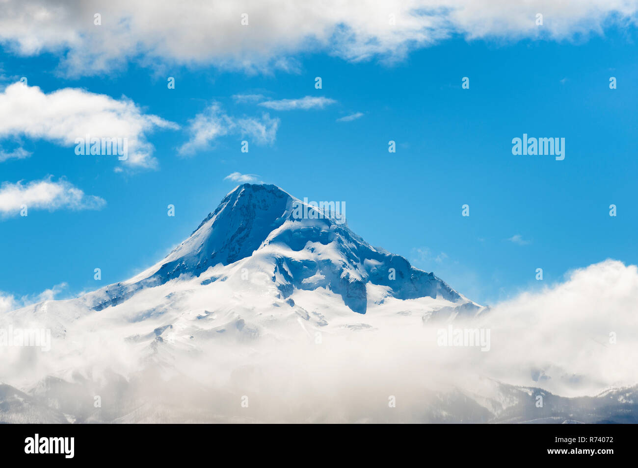 Mt. Hood peak above a layer of clouds in Oregon Cascade Range. - Stock Image