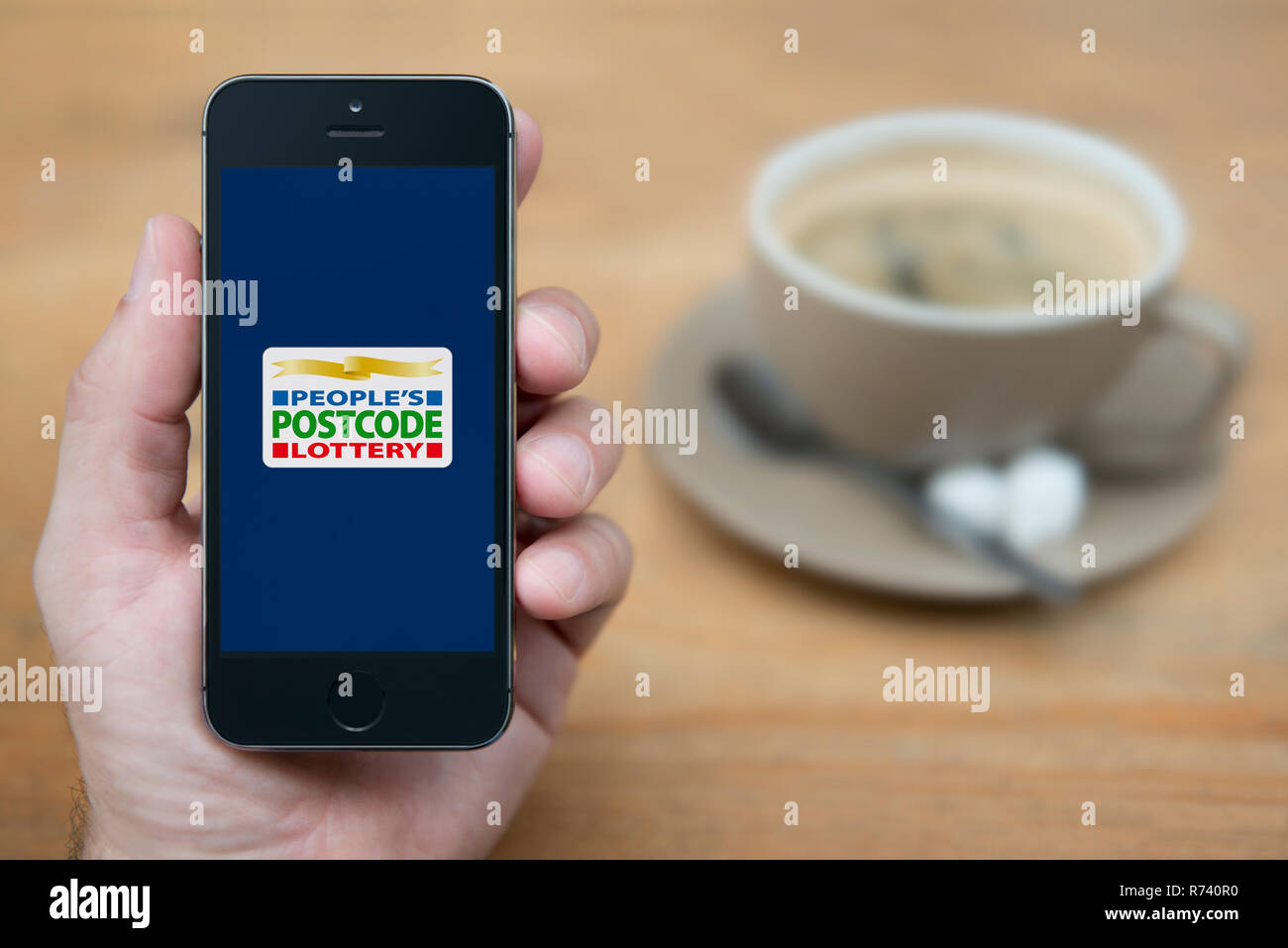 A man looks at his iPhone which displays the People's Postcode Lottery logo (Editorial use only). - Stock Image