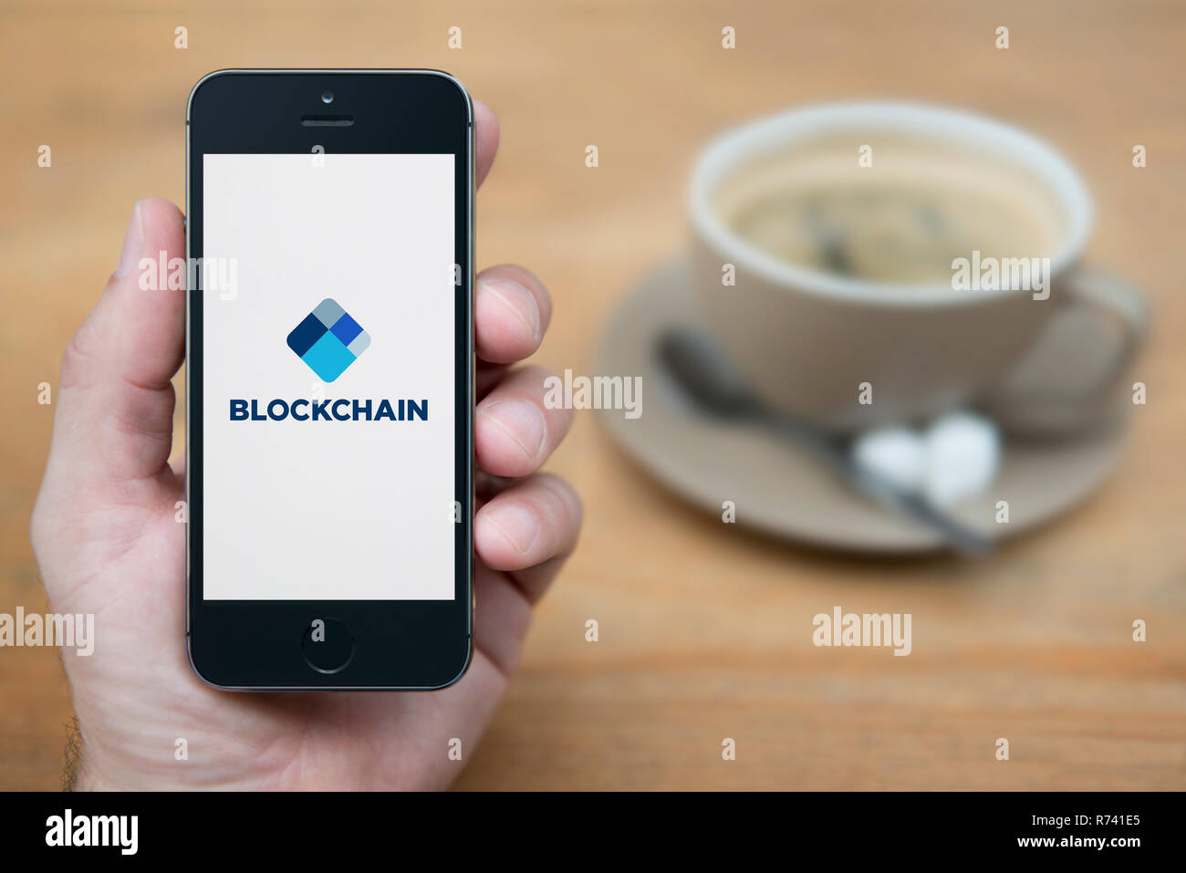 A man looks at his iPhone which displays the Blockchain logo (Editorial use only). - Stock Image