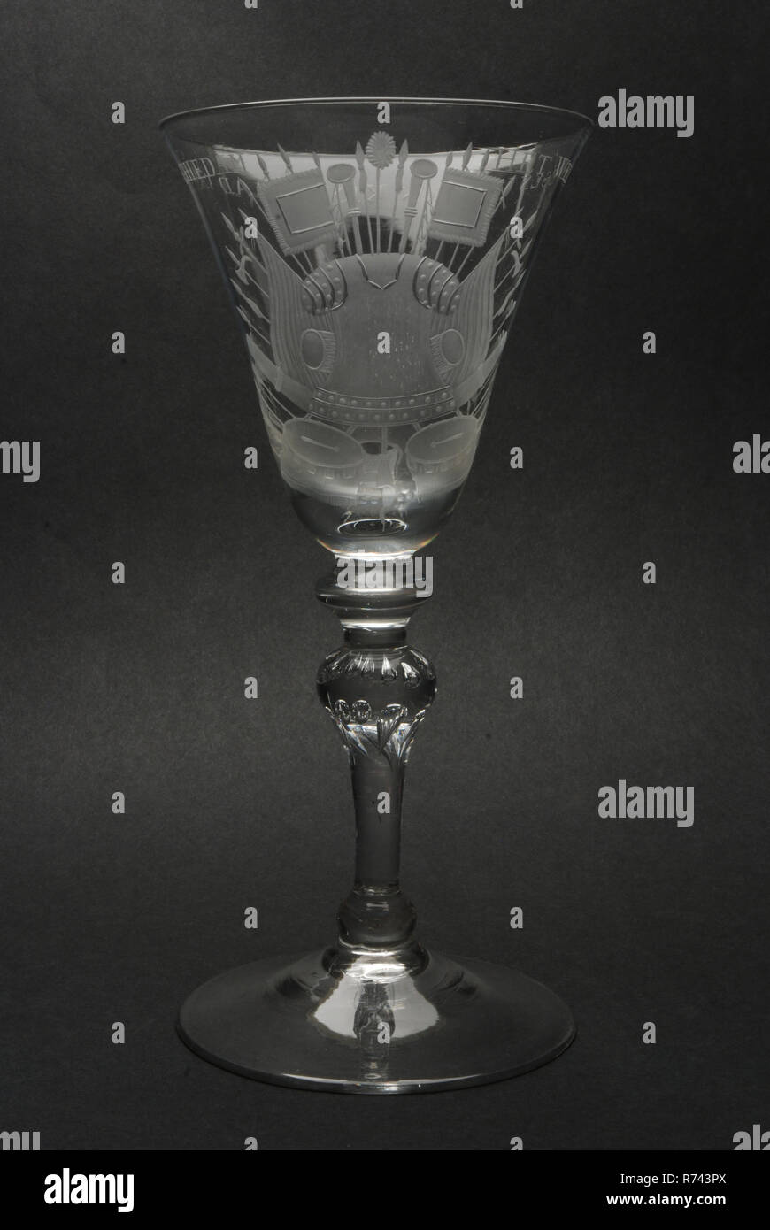 Goblet engraved with militaria and The well-being of the Krygsraad of Schiedam, wine glass drinking glass drinking utensils tableware holder lead glass glass, gram free blown and shaped radgraving polishing goblet wineglass in clear colorless lead pane Pontil mark under round hollow ascending foot On massive convex knot inverted balustersteam ('light baluster') with two rows of trapped air bubbles (lower teardrop and top convex) to flattened knot. Trumpet-shaped chalice widening upwards with the wheel engraved representation of armor surrounded by various military attributes such as spears, ha - Stock Image