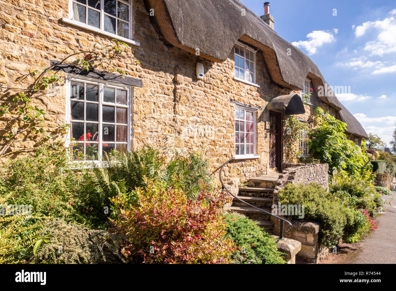A thatched stone cottage in the Cotswold village of Ebrington, Gloucestershire UK - Stock Image