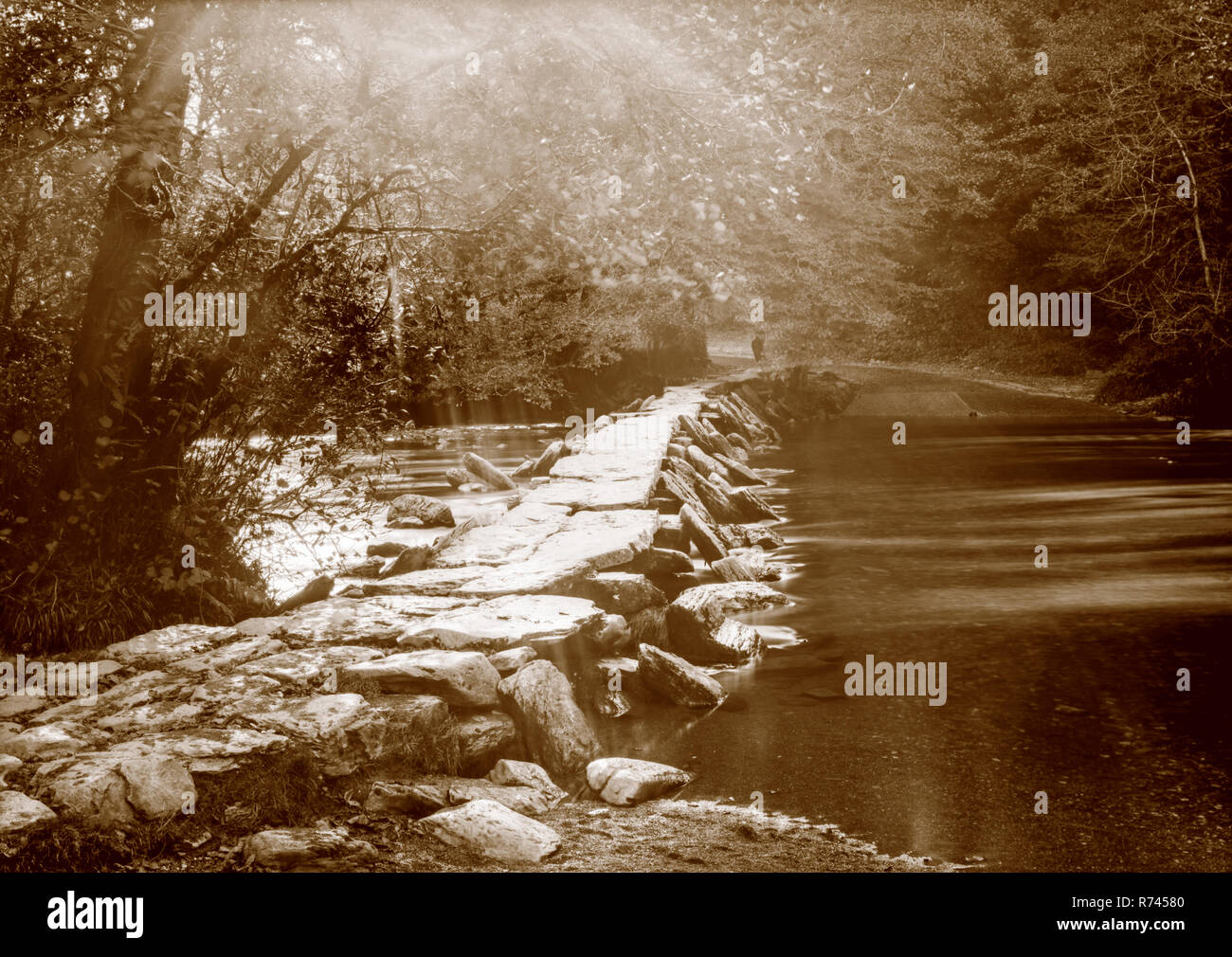 A sepia toned photograph taken on a paper negative in a 7 x 5 inch plate camera in October 2018 of the River Barle at Tarr Steps on Exmoor, Somerset U - Stock Image