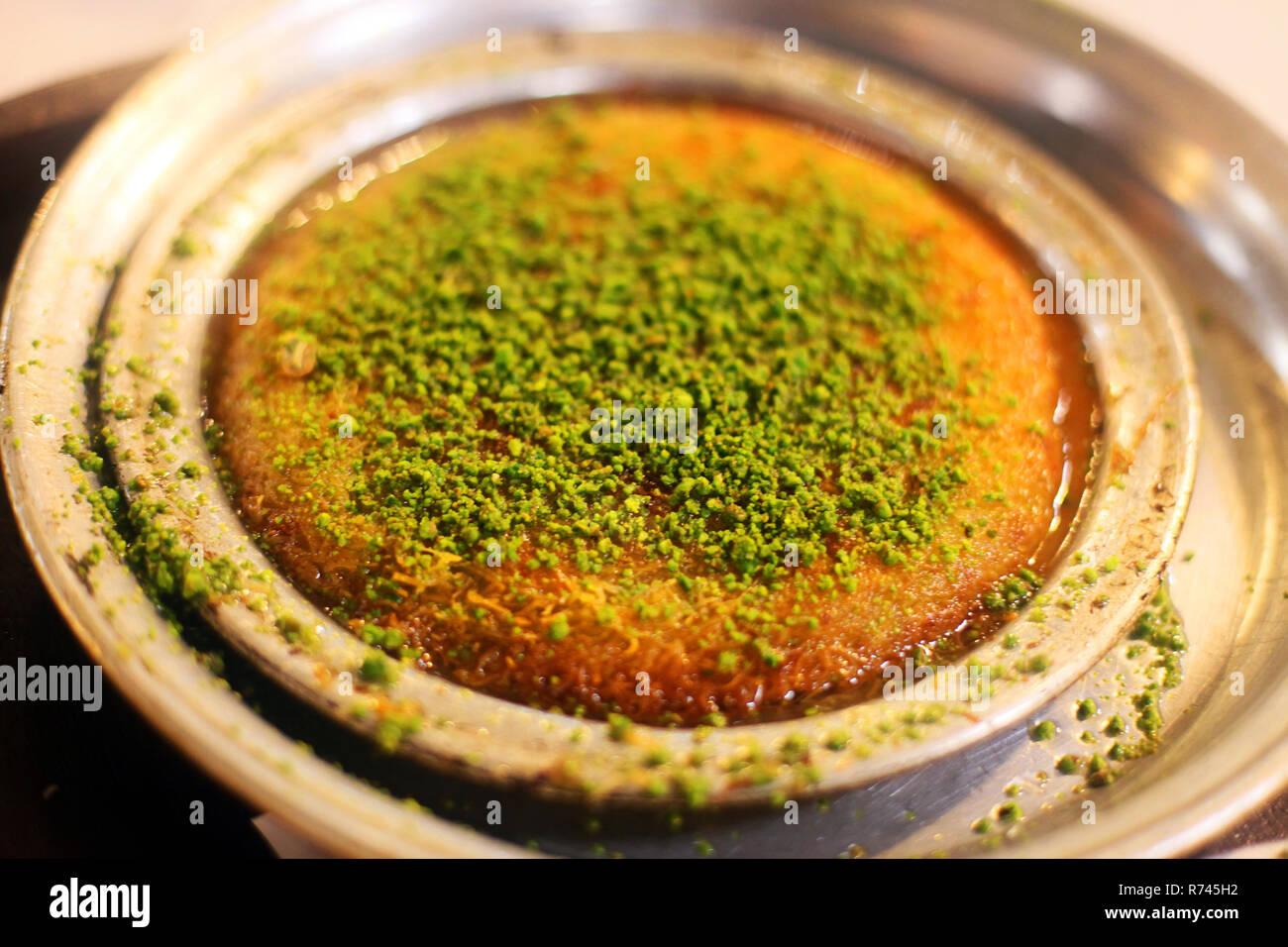 Traditional Turkish dessert 'Kunefe' in the restaurant table in Antakya, Turkey. Stock Photo
