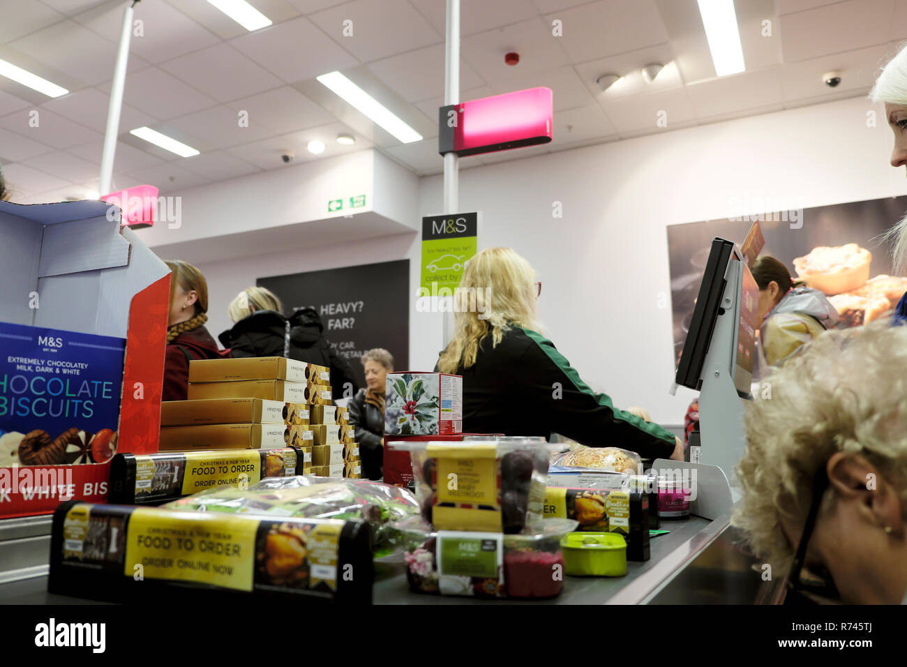 An older female worker working on the checkout counter in M&S Marks and Spencer food grocery store in Great Britain UK. KATHY DEWITT Stock Photo