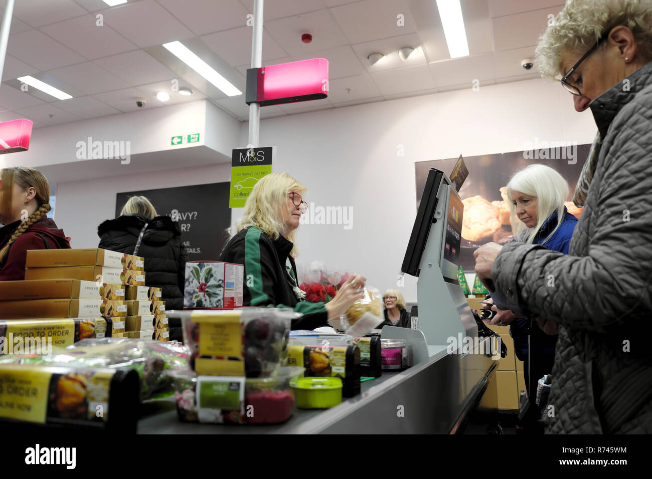 An older woman worker working at the checkout counter during Christmas  in M&S Marks and Spencer food grocery store in Great Britain UK. KATHY DEWITT Stock Photo