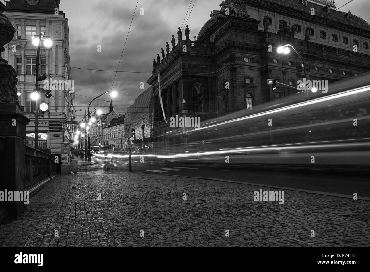 Car light trails in the city, traffic in Prague, black and white by night with street lights on. Horizontal, low angle view. - Stock Image