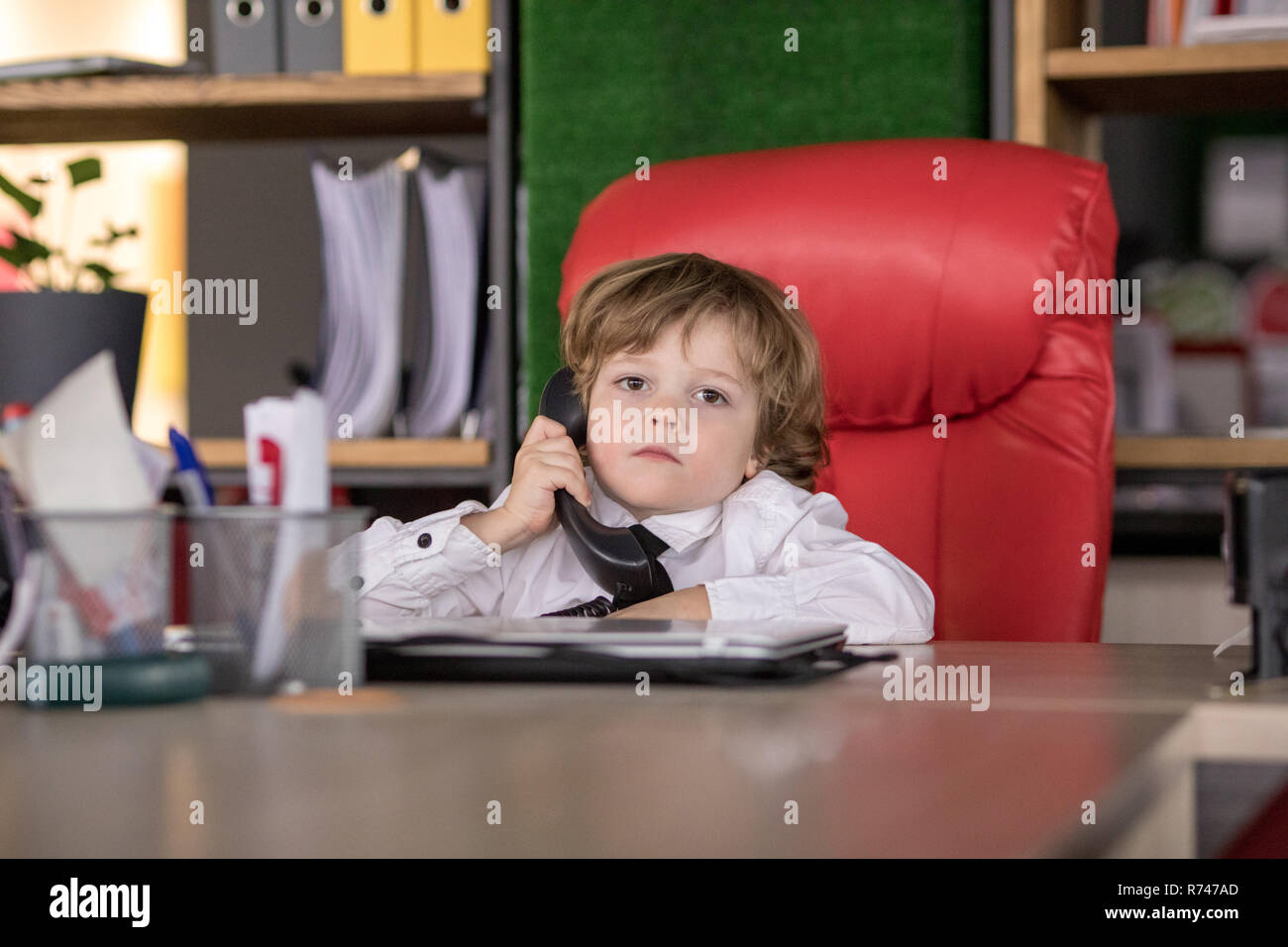 Outstanding Little Boy Sits In The Office In The Chair And Talking On Theyellowbook Wood Chair Design Ideas Theyellowbookinfo