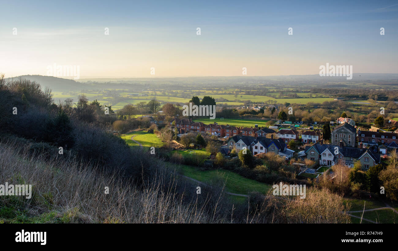 Winter sun illumates a patchwork of farmland fields, woodland and villages in North Dorset's Blackmore Vale, as viewed from Shaftesbury's Castle Hill. - Stock Image