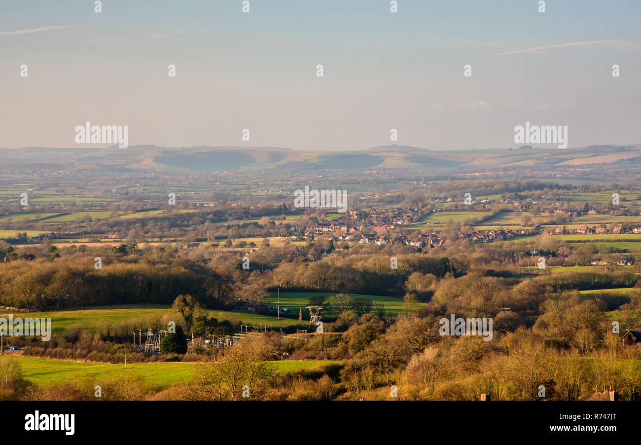 A patchwork of farmland fields, woods and villages covers the agricultural plain of the Blackmore Vale, beneath the hills of the Wiltshire Downs, as v - Stock Image