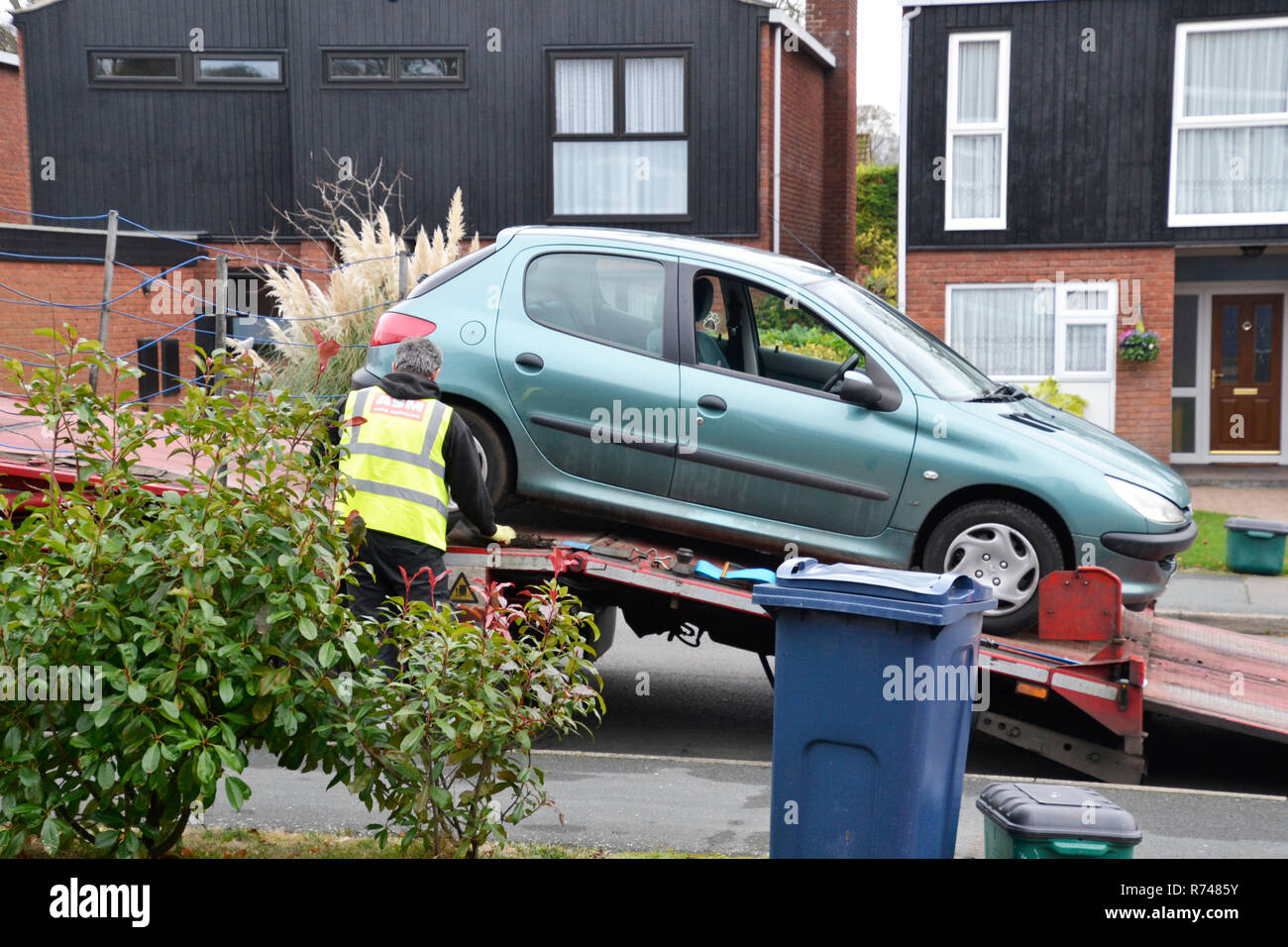 Car being loaded onto lorry, destined for the scrap yard, recycling, at the end of its life - Stock Image