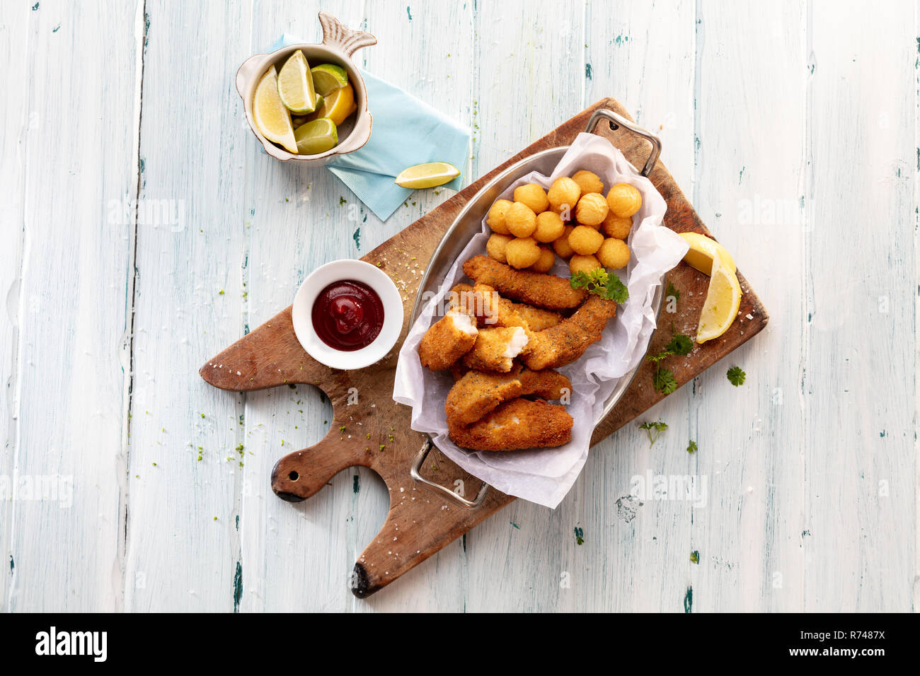 Cheese croquettes and potato balls on cutting board with tomato sauce , still life, overhead view - Stock Image