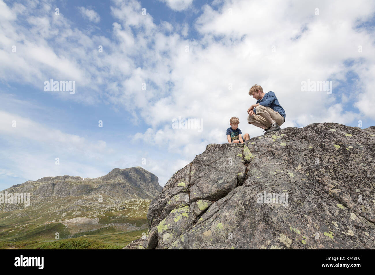 Boy and father crouching on top of rock formation, low angle view, Oppland, Nord-Trondelag, Norway - Stock Image