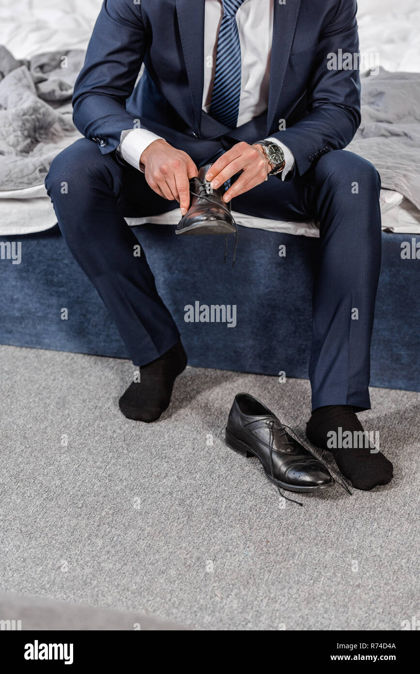 Cropped Image Of Man In Suit Wearing Shoes And Sitting On Bed In Morning In Bedroom Stock Photo Alamy