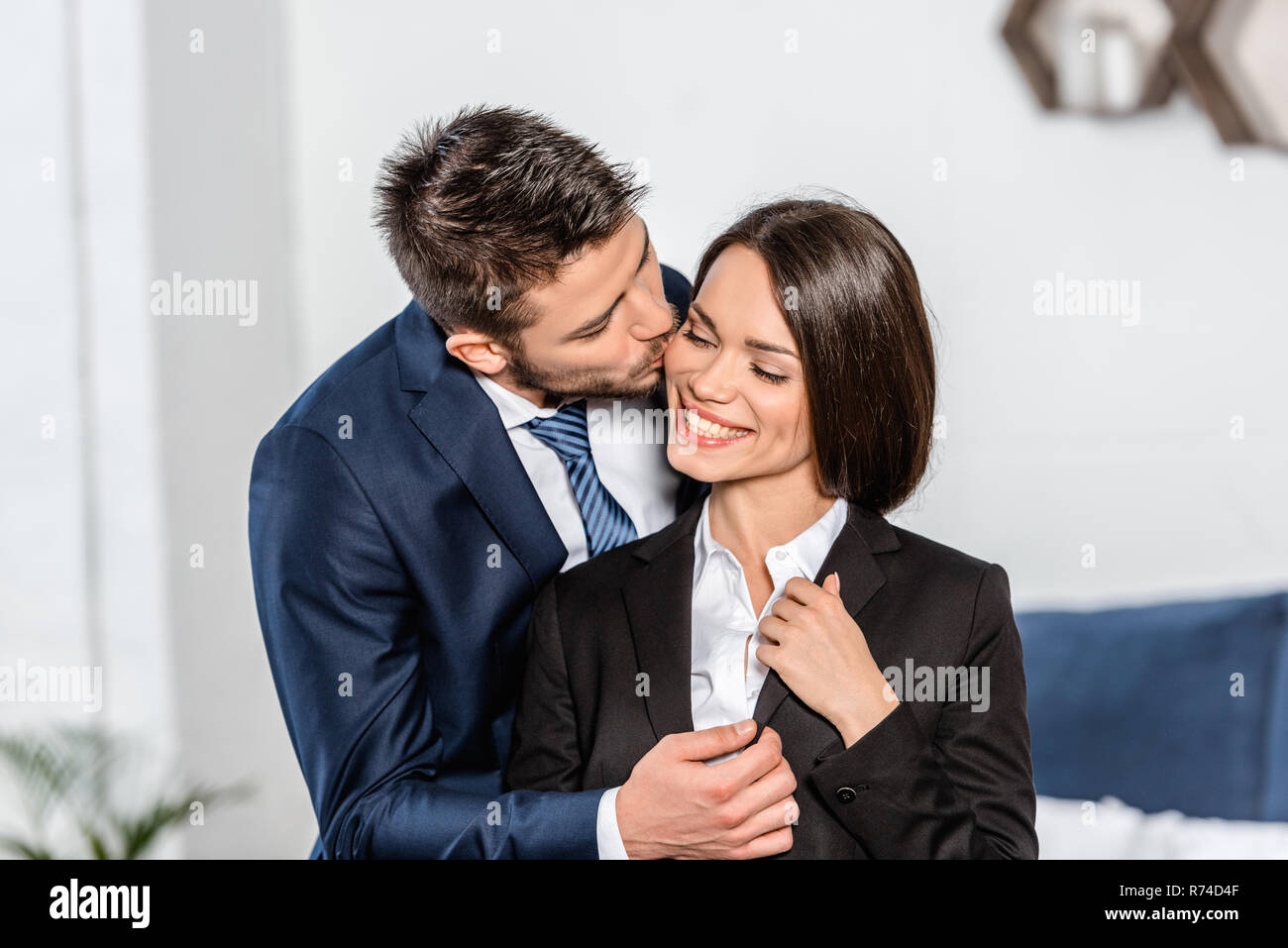 handsome boyfriend kissing smiling attractive girlfriend before work at home - Stock Image