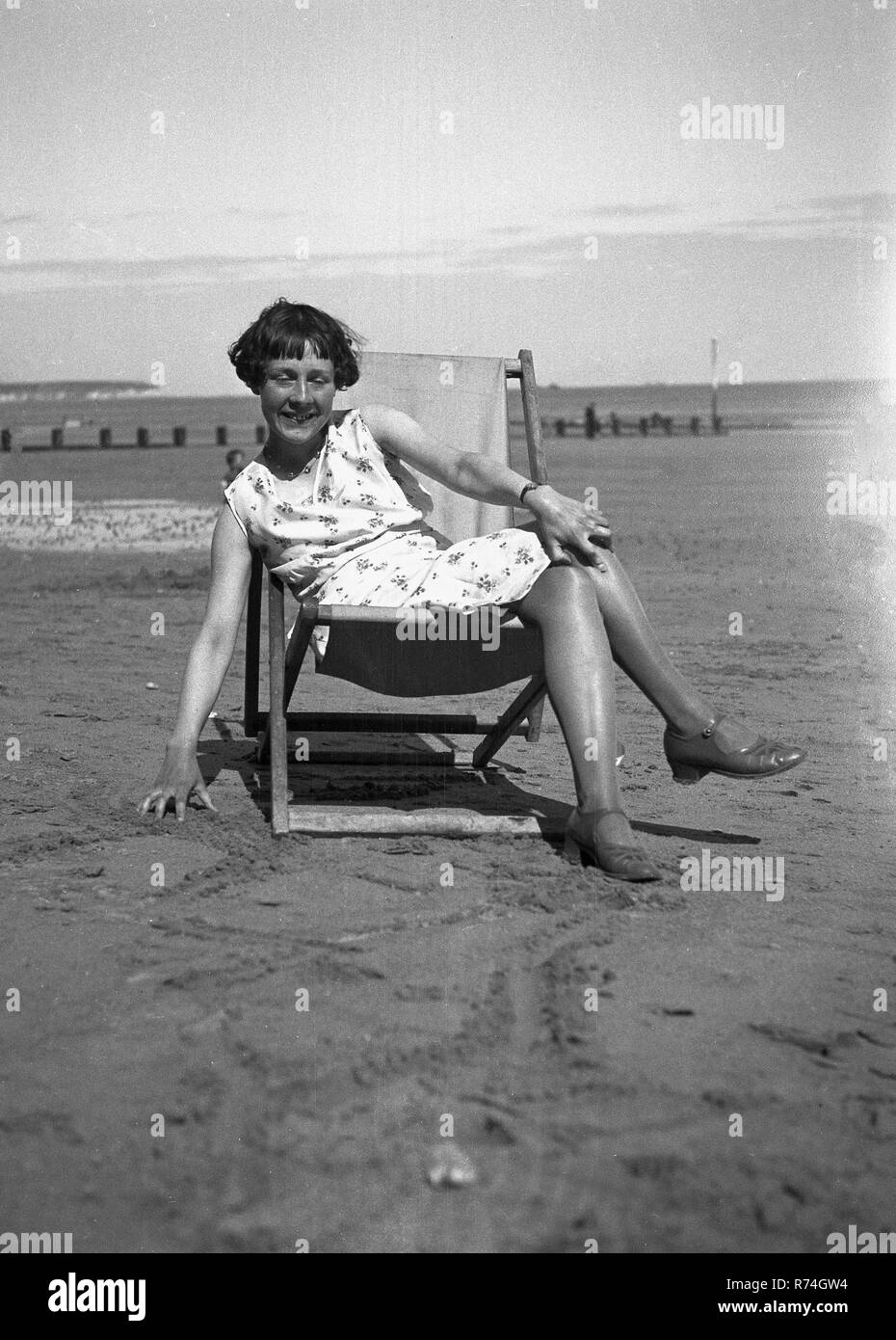 1930s, historical, young woman in a deckchair on a sandy beach. Stock Photo