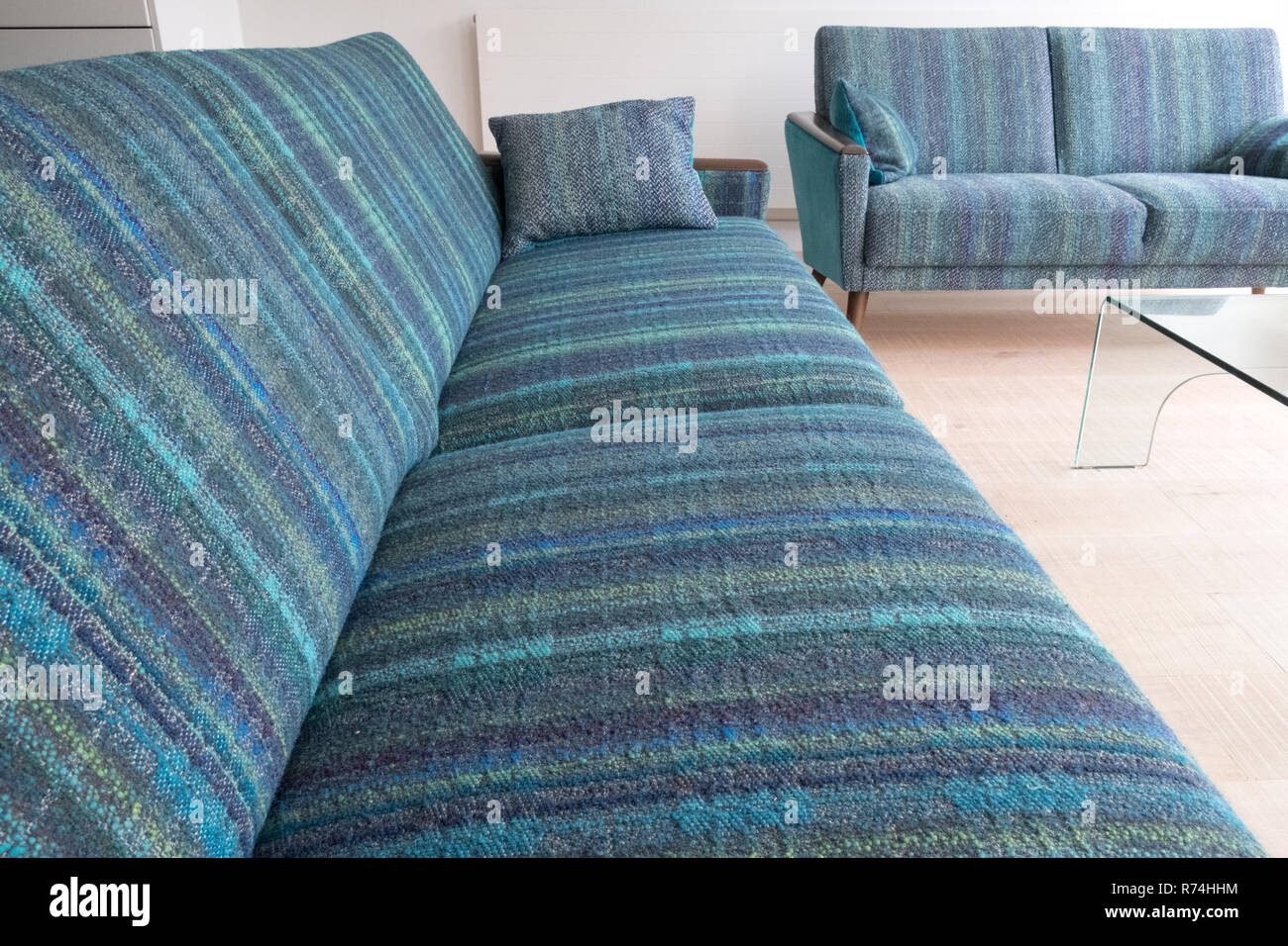 Two retro style lounge sofas upholstered in blue / green striped wool fabric - Stock Image