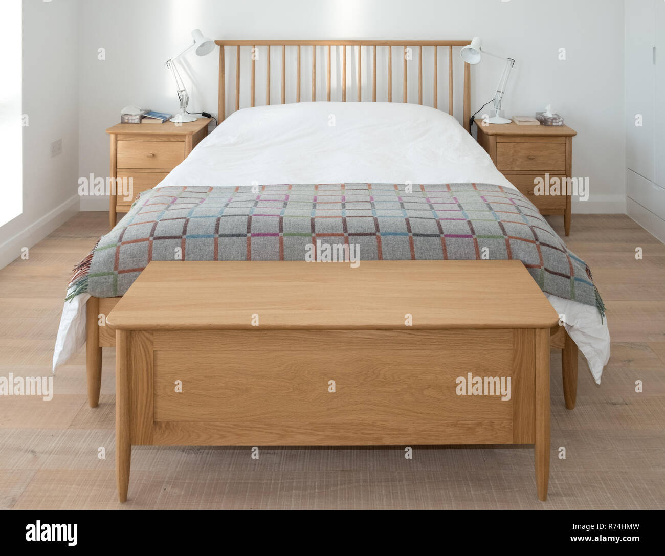 Scandinavian Inspired Minimalist Bedroom Interior Showing Wooden Bedroom Furniture White Painted Walls White Bedding And Colourful Blanket Stock Photo Alamy