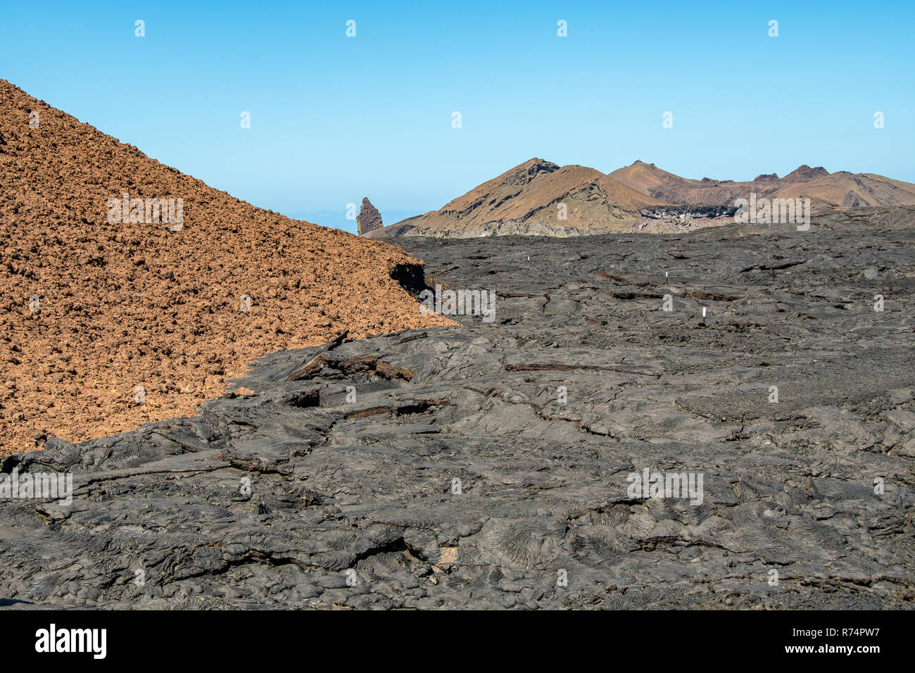 The gray lava flow of the Santiago island in the Galapagos contrasts with the red of the rocks - Stock Image