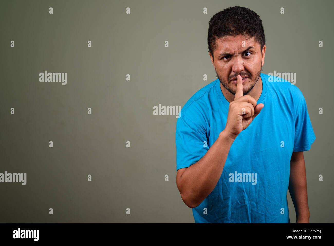 Bearded Persian man wearing blue shirt against colored backgroun Stock Photo