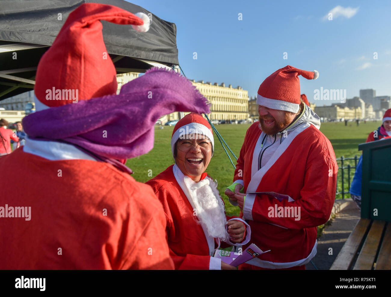 Brighton, Sussex, UK. 08th December 2018. Hundreds of Santas take part in the annual Brighton Santa Dash in windy weather along the seafront at Hove raising money for the local Rockinghorse charity . Rockinghorse is a Brighton-based charity that has been supporting children in Sussex for over 50 years. Credit: Simon Dack/Alamy Live News - Stock Image