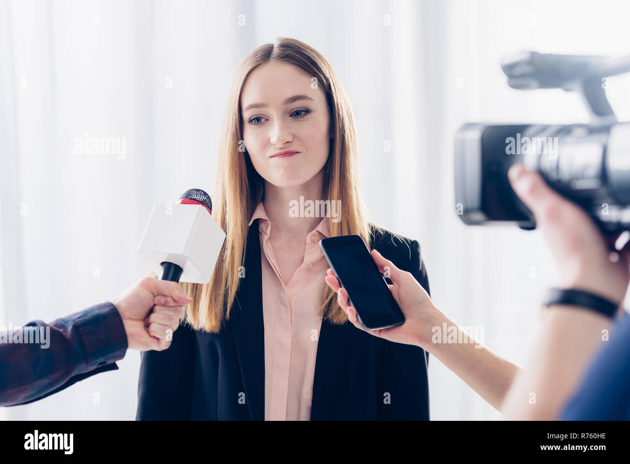 grimacing businesswoman giving interview to journalists in office - Stock Image