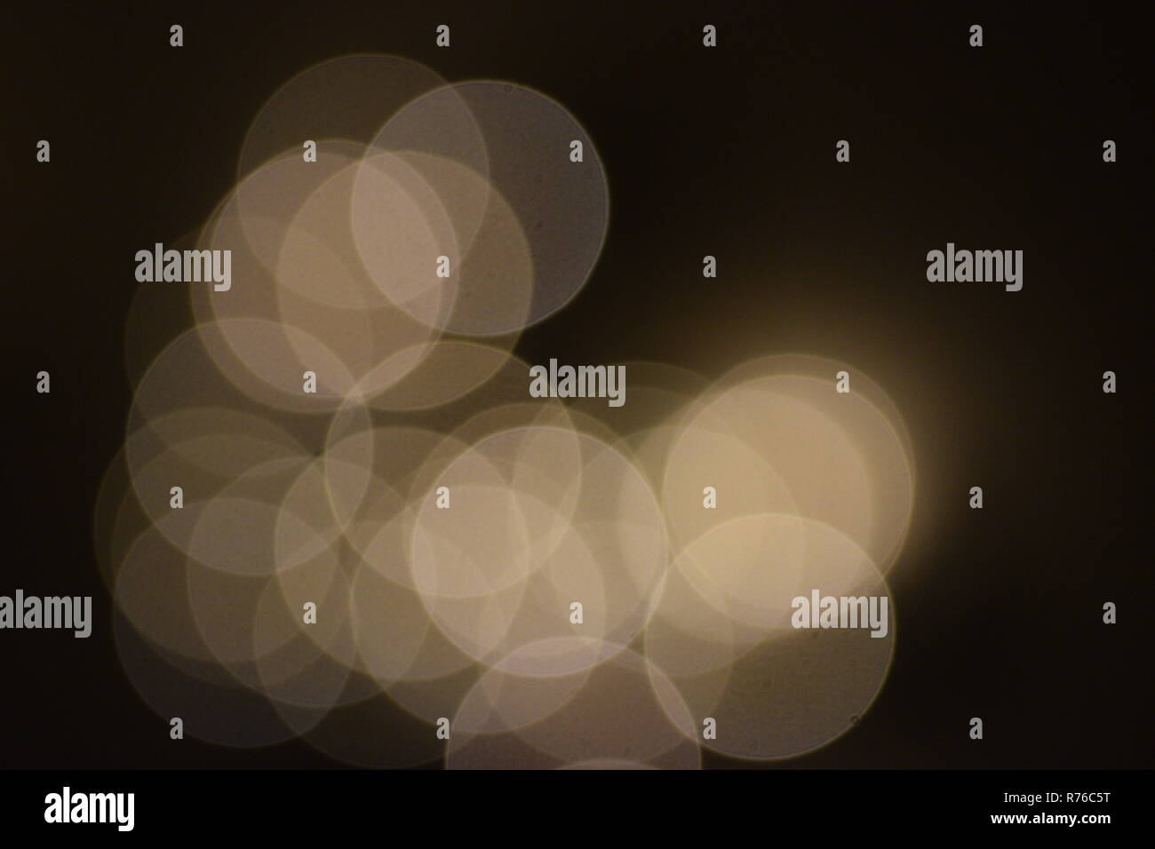 many bright blurry circles overlapping against dark background, design element - Stock Image