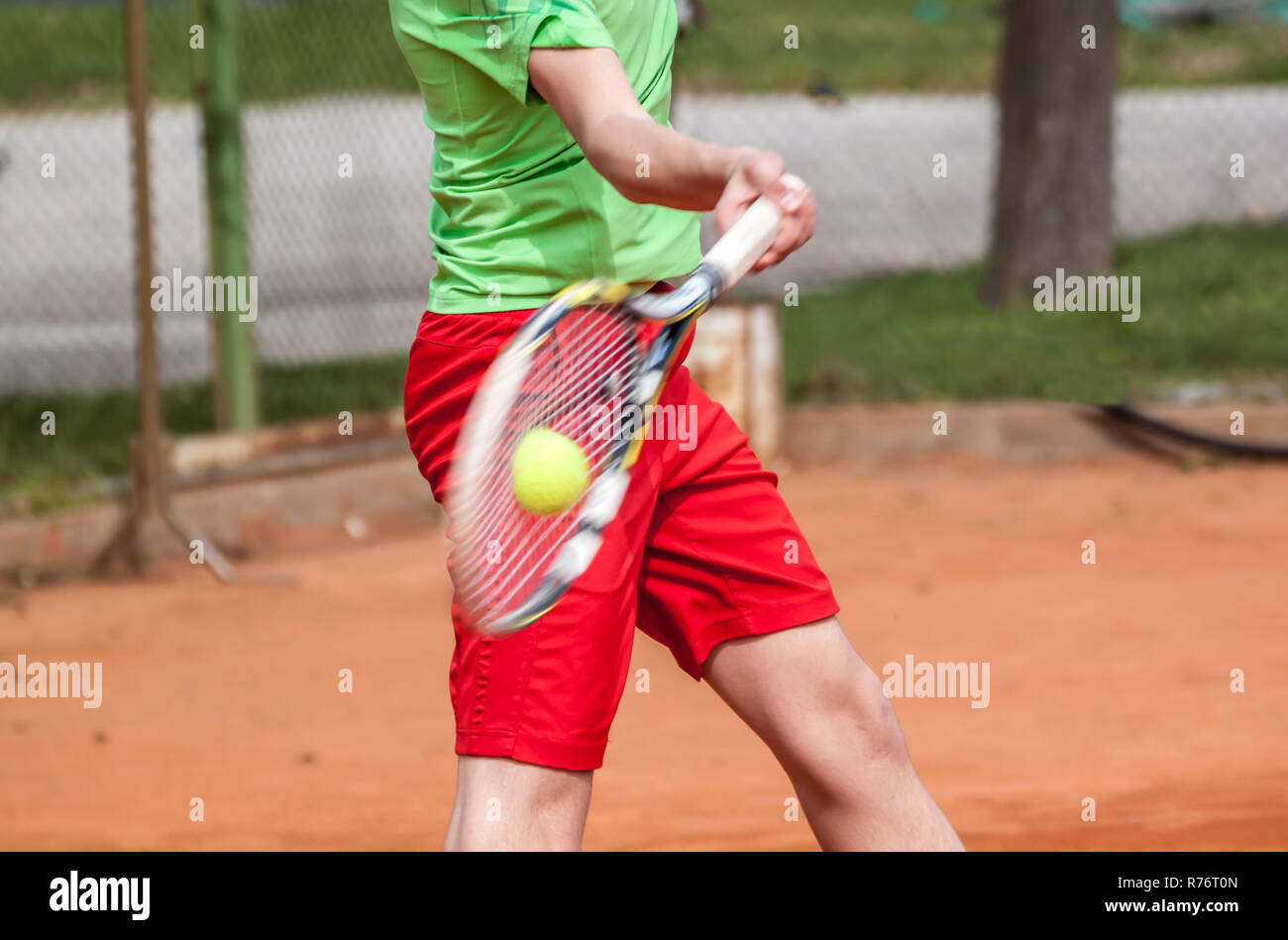 Tennis racket cord and ball deforming from the power of a forehand strike. - Stock Image