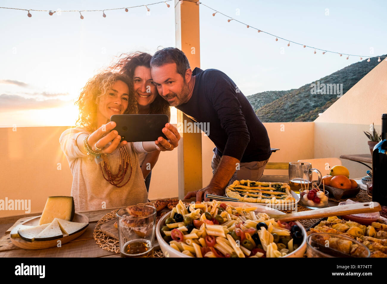 Group of people friednship concept have fun together taking selfie during a dinner or lunch outdoor at home in the terrace - firends and caucasian wom - Stock Image