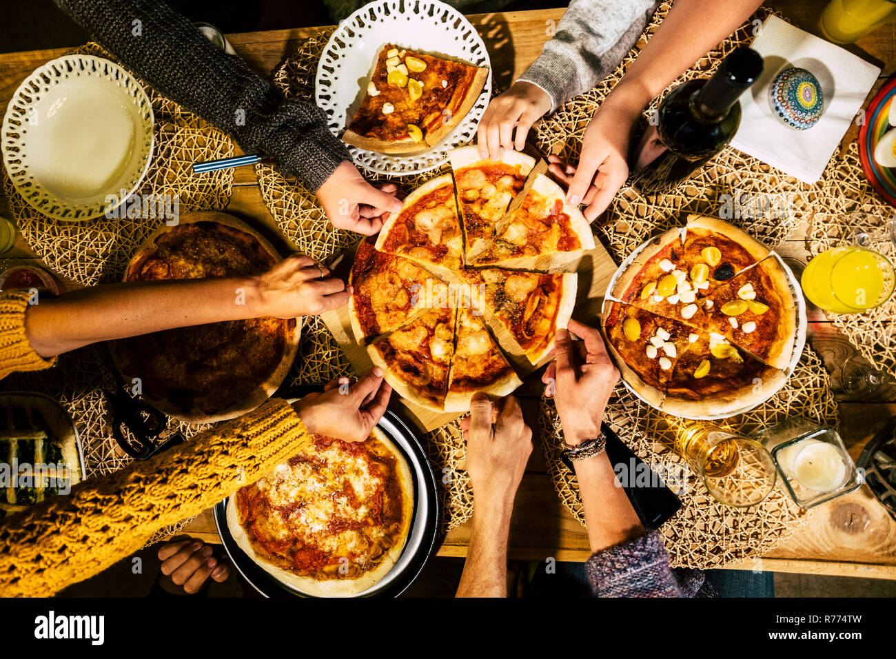 People eat pizza at festive table served for party. Friends celebrate with catering food on wooden table top view. Woman and man's yands take the piec - Stock Image