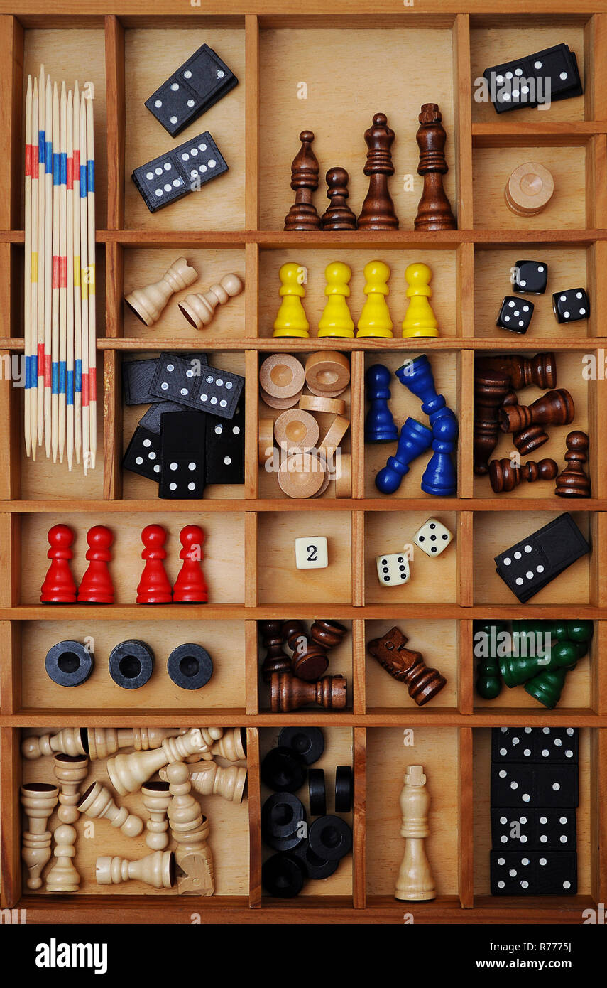 Wooden figures of board games, gaming pieces, dice, dominoes, Mikado sticks, games collection in a letter case Stock Photo