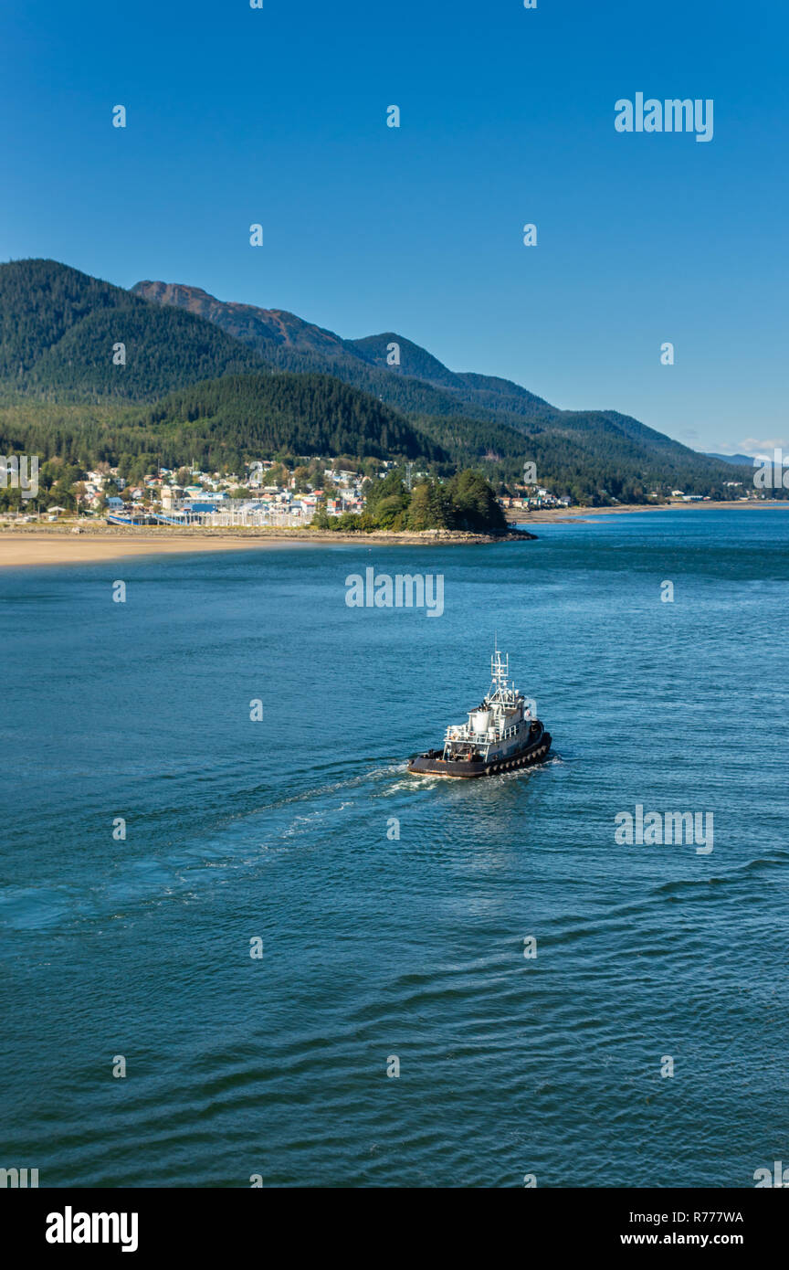 Local working tugboat heading North bound in to port on a bright clear sunny day. Gastineau Channel, Juneau, Alaska, USA. Eastetn shore of community o - Stock Image