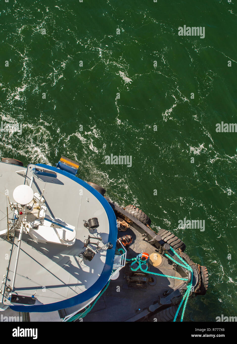 Overhead POV view of tugboat, ropes and workers assisting large ship to dock in high winds on a bright sunny day. Gastineau Channel, Juneau, Alaska, U - Stock Image