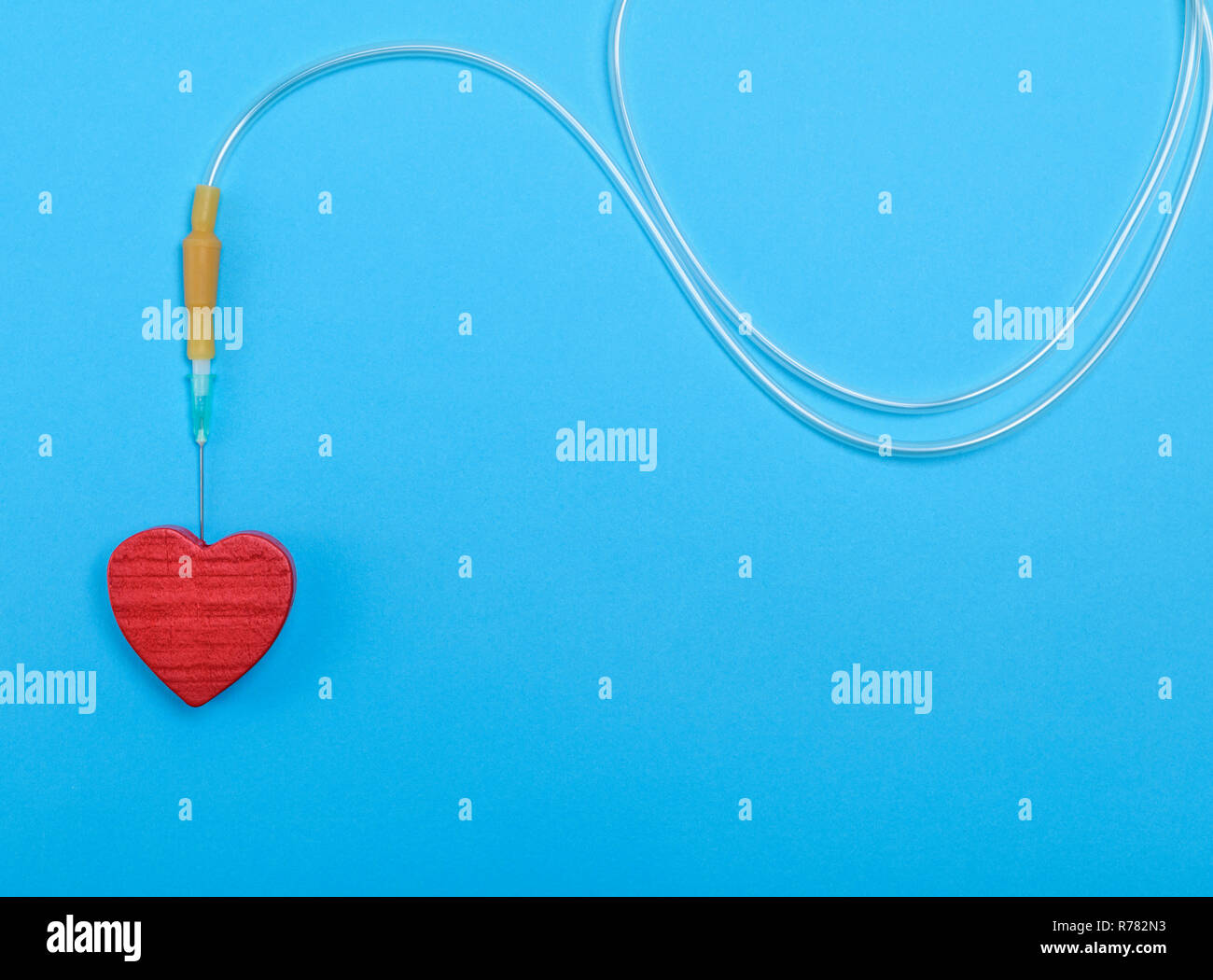 plastic catheter with needle and red heart - Stock Image