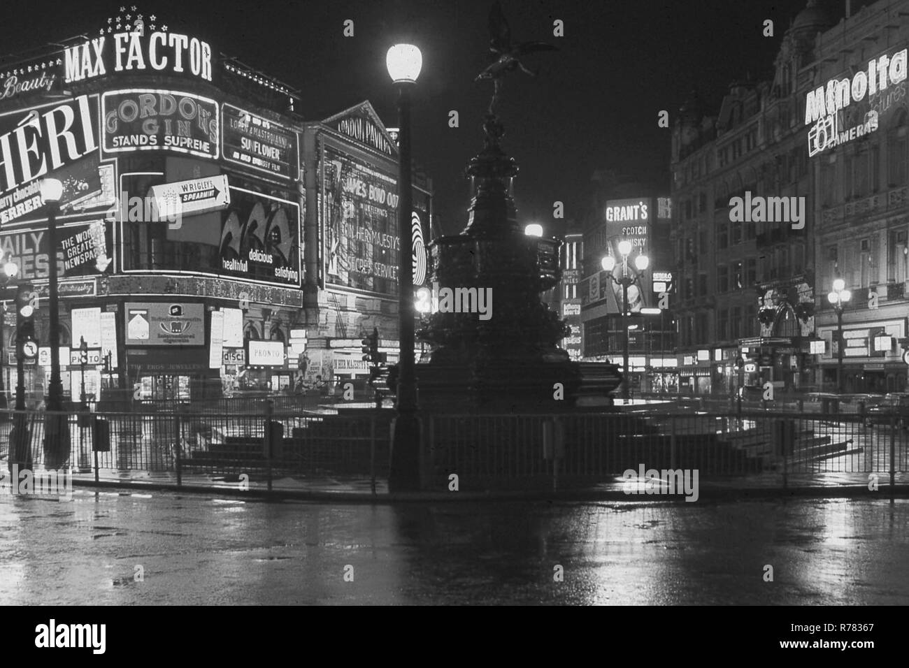1969, a wet central London night, seen here is the Shaftesbury Memorial Fountain, more commonly known as statue of eros at Piccadilly Circus, with the neon lights of the surrounding advertising billboards. Showing at the London Pavilion, the new James Bond film, 'On Her Majesty's Secret Service', the sixth film in the Bond 007 series. - Stock Image